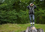 Man Using Binoculars on Tree Stump