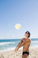 Hispanic man playing volleyball at beach