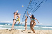 Multi_ethnic friends playing volleyball at beach