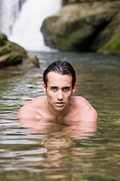 Hispanic man swimming in stream