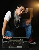 Hispanic man crouching near boom box