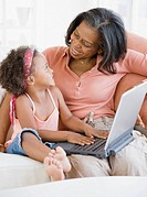 African grandmother teaching granddaughter how to use laptop