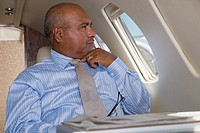 Hispanic businessman thinking on private jet