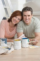 Smiling couple picking out paint colors