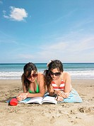 Two young woman sharing a book