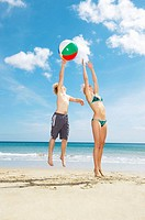 Young couple leaping for beach ball