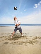 Young man with football on beach (thumbnail)