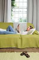 Young woman texting on couch (thumbnail)