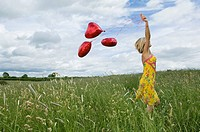 Woman walking with balloons in field (thumbnail)