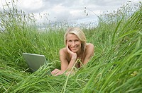 Woman lying in field with laptop