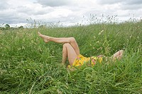 Woman lying in field showing legs