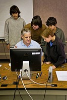 Middle school students watch the monitor as their computer class teacher shows them new software (note Hispanic student at left)