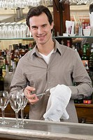Male bartender drying wine glasses