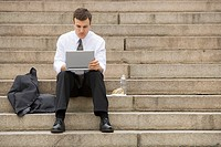 Young adult male sitting outdoors on stairs with laptop