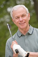 Portrait of senior man with golf club