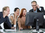 Group of businesspeople cheering with computer