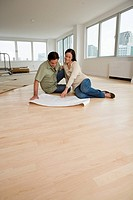 Couple looking at blueprints on floor in new house