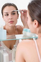 Woman combing eyebrows in mirror