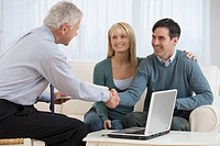 Businessman shaking hands with couple in home