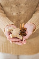 Close up of woman holding ginger root and spices