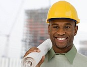 Portrait of man in hard hat holding blueprints