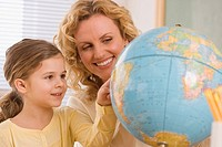 Mother and daughter looking at globe