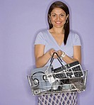 Indian woman holding shopping basket with electronics