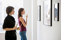 Two women looking at artwork in gallery