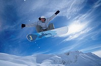 Young man jumping with snowboard