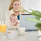Mother holding baby and using laptop