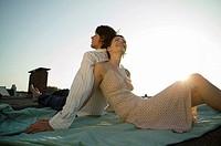 Couple sitting on blanket, leaning back to back
