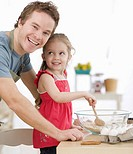 Father and daughter mixing batter in kitchen