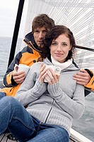 Germany, Baltic Sea, Lübecker Bucht, Young couple on sailing boat sitting and holding mugs, portrait
