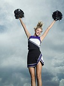 Cheerleader with pom poms jumping
