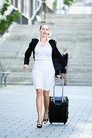 Germany, Baden_Württemberg, Stuttgart, Businesswoman walking with case, in a hurry