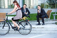 Germany, Baden_Württemberg, Stuttgart, Woman cycling, businessmen watching