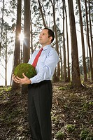 Hispanic businessman holding ball of moss