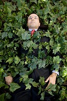 Hispanic businessman covered in ivy