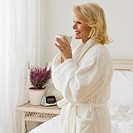 Senior woman in bathrobe drinking coffee