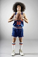 Mixed race basketball player holding basketball