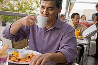 Mixed race man drinking coffee in restaurant