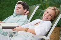 Couple relaxing in lounge chairs