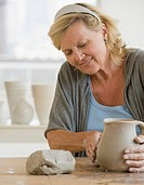 Senior woman making ceramic pot