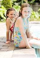 Girls sitting on edge of swimming pool