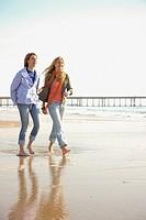 Two women walking on beach