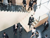Businessman leaning on busy office staircase