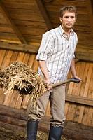 Farmer shovelling hay in barn