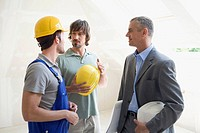 Two men talking to Architect at construction site