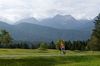 Germany, Bavaria, Mittenwald, Woman mountain biking against mountain scenery