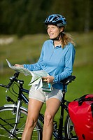 Germany, Bavaria, Mittenwald, Woman leaning against mountain bike, holding map